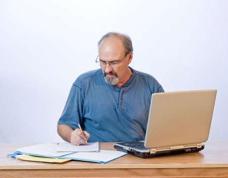 A businessman takes notes from the computer search results. Stock Photo - 3735263