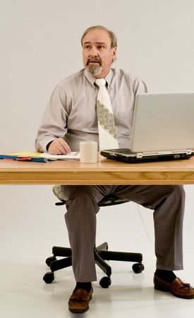 A businessman seated at a desk while attatched to an oxygen concentrator. 版權商用圖片