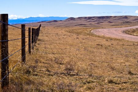 A barbed wire fence runs along a gravel road, east of the Rocky Mountains Stock Photo