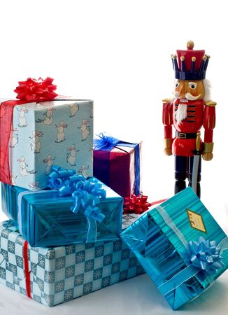 An  oversized nutcracker stands near a small pile of presents. photo