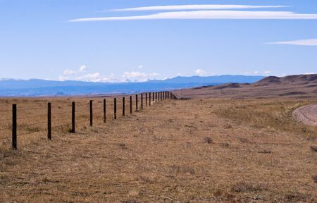Rocky Mountains in the background of a high plains drift fence. Stock Photo - 3815330