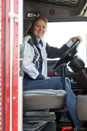 View of woman truck driver from the passenger side of the truck.