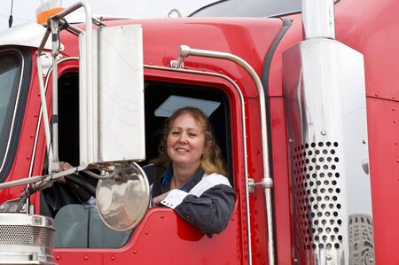 leaning on the truck: Woman truck driver leaning out the drivers side window. Stock Photo