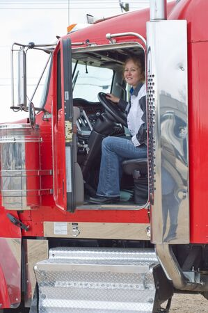 truck: A woman truck driver seated in the drivers seat of a big truck.