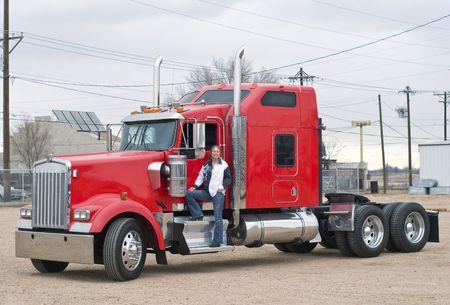truck driver: A pretty woman prepares to pre-trip inspect her truck.