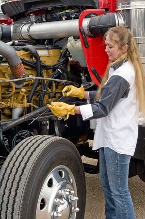 truck driver: A driver doing her pre-trip inspection prior to leaving.