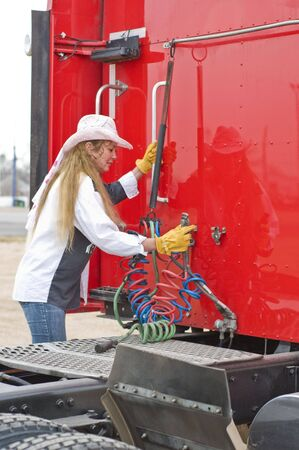 A woman hangs up the air lines after dropping off her trailer.