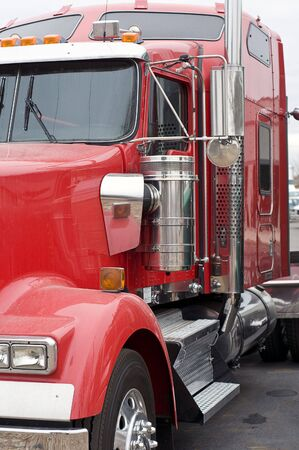A shiny red big truck  ready to haul a loaded trailer.