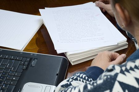 An author studing proofreaders marks on her manuscript.