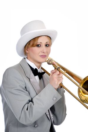 Pretty woman posed with a trombone while wearing a tuxedo and top hat.
