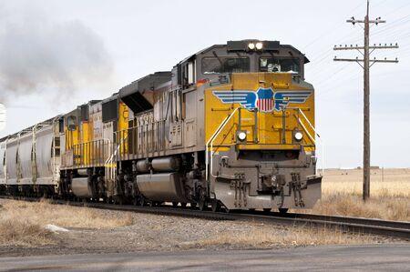 needing: A freight train, needing a wash smokes through the countryside.