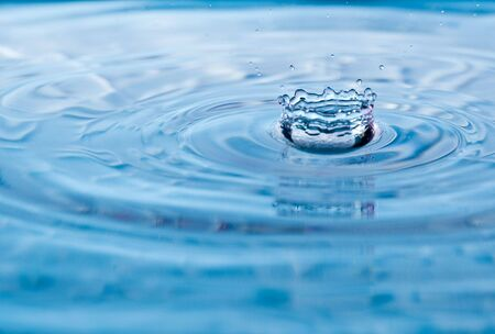coronet: Red tint to a water drop splash with coronet shape Stock Photo