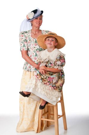 social history: Early twentieth century clothing modeled by cute little girl and her grandmother Stock Photo