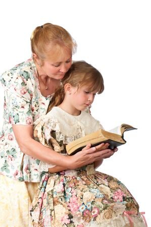 A pretty woman helps her granddaughter read from an old family Bible.