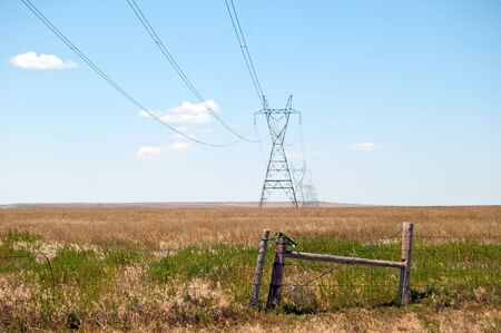High voltage lines planted across the prarie over and old barbed wire fence. photo