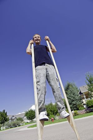 zancos: Muchacho adolescente aprender a caminar sobre sus zancos de fabricaci�n casera. Foto de archivo