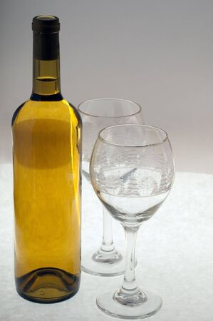 Two glasses ready to fill from a new unopened bottle of white wine. Stock Photo - 5519863