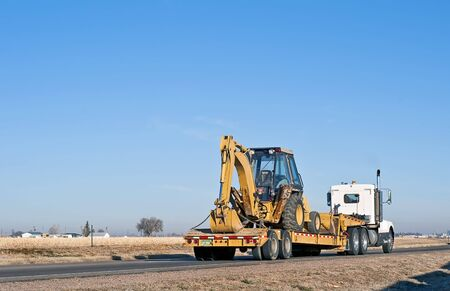 Big truck with a drop-deck trailer hauling a back-hoe tractor. Stock Photo