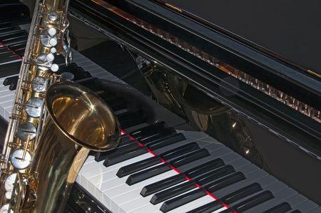 Closeup of a tenor sax against a black grand piano