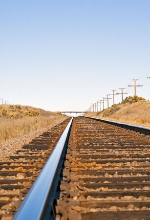Railroad track across empty rural country giving the sense of time and distance.