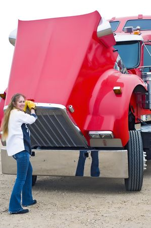 Woman truck driver opens the hood of her semi-truck to check the oil and other fluid levels before starting her trip. photo