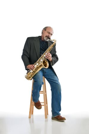 the tenor: Adult male playing a tenor saxaphone while seated isolated on pure white.