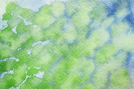 Blue colors slipping in with the green watercolors on textured paper