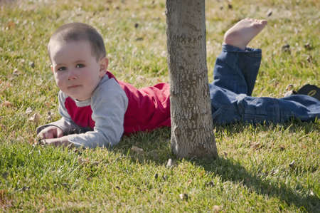 Little boy resting from busy time playing in the back yard. Stock Photo