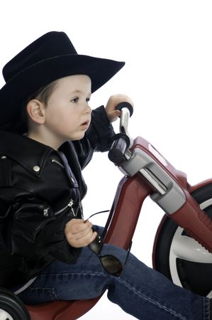 Baby boy in his new leather biker jacket riding his new trike. photo
