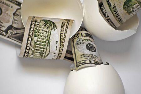 fake money: Broken egg shells with fake money representing broken nesteggs. Stock Photo