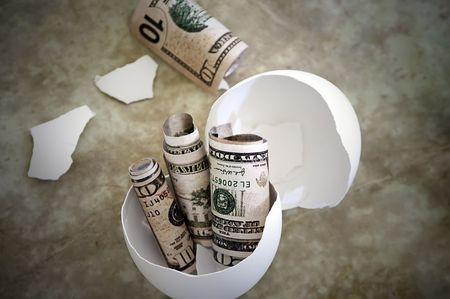 nestegg: Money newly hatched from a broken nest-egg, representing accumulated savings. Stock Photo