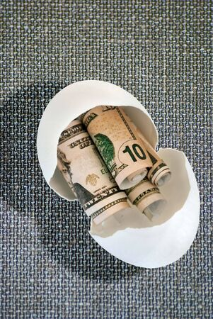 nestegg: Burlap background with fake money in a  broken egg to represent opening a nest-egg.