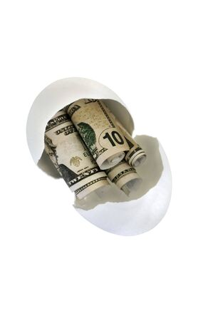 nestegg: Broken egg shell with rolled up fake money to represent getting into a persons nest-egg.