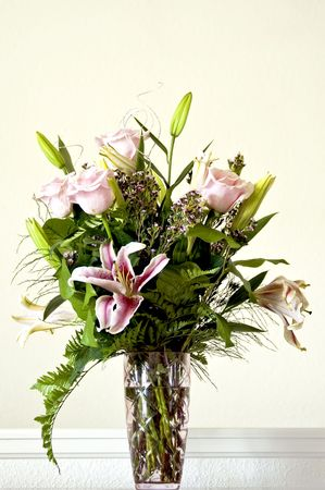 Bouquet of lilies and pink roses arranged in a clear glass vase. Stock Photo