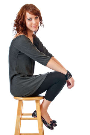 stool: Beautiful young woman seated on a kitchen stool against a white background