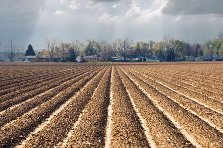 rural town: Newly planted ground on the edge of a rural town about to recieve fresh rain to bring the crop out of the earth. Stock Photo