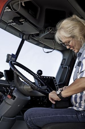 trucker: Woman truck driver getting out her log book and getting ready to start her trip.