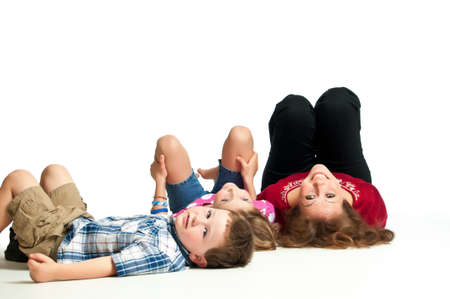 thier: Young brother and sister playing on the floor with thier beautiful mother against a white background. Stock Photo