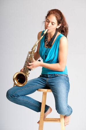 barefooted: Pretty brunette girl practicing on the saxophone while seated barefooted on a stool Stock Photo
