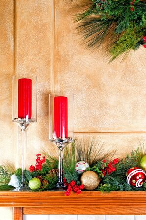 Fireplace mantle decorated with candles and garlands for Christmas