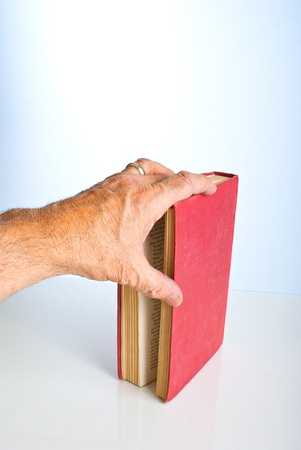 Left male hand marking his place with his finger in a book.