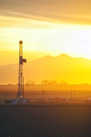 Oilrig drilling at sunset under Longs Peak in the Rocky Mountains