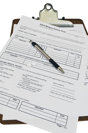 Medical history forms on a clipboard with two small pills sitting on the form with a pen.  Stock Photo