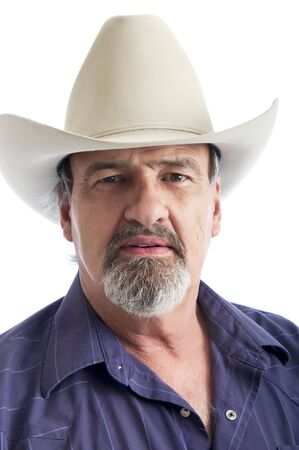sternly: Adult man wearing a cowboy hat looking sternly at the camera