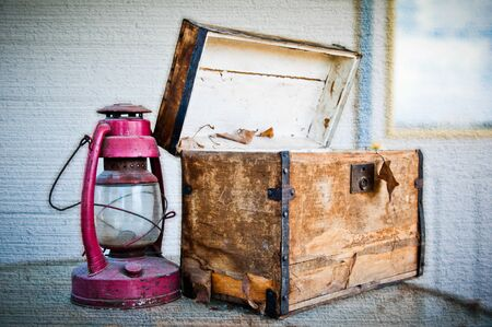 kerosene: Worn out chest and old lantern on a textured background