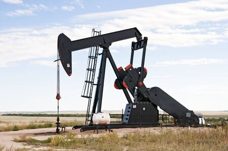 Pump jack starting the lifting stroke to brink crude oil up out of a producing oil well. photo
