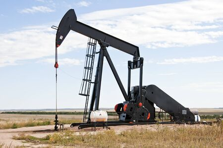 Raised pump jack in south central Colorado, USA, ready to start the down stroke to load the lifting pump with crude oil. Stock Photo