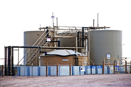 Treatment and storage tanks for separating water from condensate at a gas and oil well location.