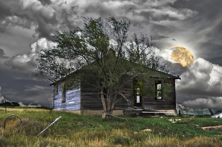 deserted: Abandoned house with a faint, dim light coming from the open doors and windows. Haunted for Halloween. Stock Photo