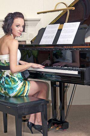 그랜드 피아노를 연주하는 매력적인 젊은 갈색 머리 여자.